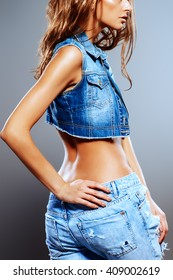 Stunning young woman in jeans clothes posing over gray background. Denim style. Fashion shot.