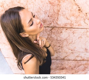 Stunning young woman standing next to a pink wall - Beautiful fashion girl
