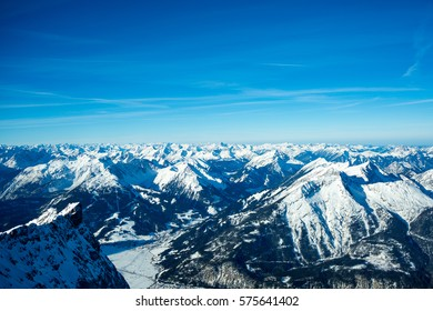 Stunningly beautiful alpine snow covered winter landscape prominently featuring the mountains Hochvogel and Santis as well as the village Lermoos in Tirol, Austria, as seen from the Zugspitze.