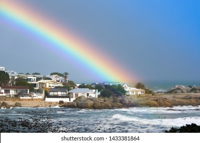 A stunningly beautiful rainbow rests over Bakoven, Cape Town, South Africa following a large storm system that came through the Cape of Storms promising a pot of gold at the end of the rainbow