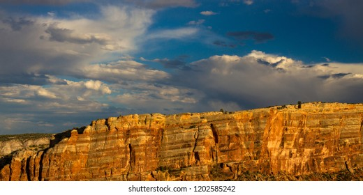 Stunningly beautiful sunset light on the steep, sloping stone cliffs of Monument Canyon in Colorado National Monument