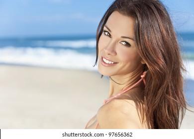 Stunningly beautiful young brunette woman in sunshine on a beach and wearing a bikini
