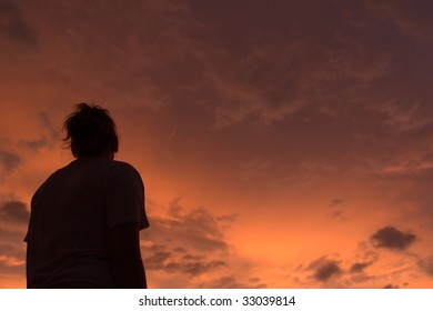 Stunningly beautifully colored sunset with the silhouette of a young woman observing.
