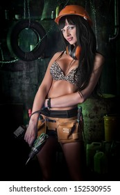 Stunningly sexy girl posing with tools in the old garage.