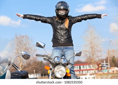 Stunt girl balancing while rides motorcycle without hands, arms extended sidewards