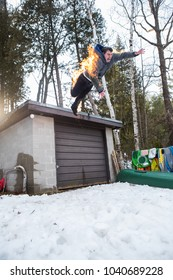 A stunt man practice in his backyard by lighting himself on fire and jumping off a garage.