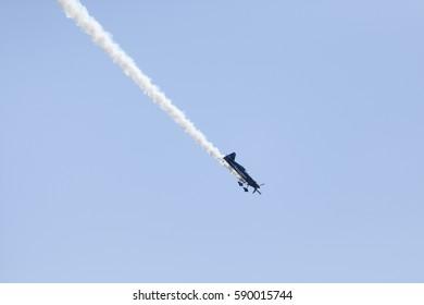 A stunt plane trailing smoke at an airshow in Stuart FL