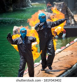 The stuntman is performing a show on fire for two.