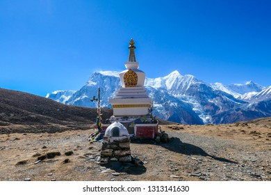 A stupa with Annapurna Chain as a backdrop, Annapurna Circuit Trek, Himalayas, Nepal. High mountains covered with snow. Land in front of the stupa is barren and dry. Some prayer's flag next to it.