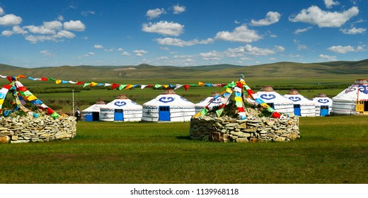 stupa of stone with prying flag, and some yurt  in the grassland of Mongolia