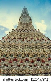 stupa-like pagoda encrusted with colorful glazed porcelain tiles and seashells in Wat Arun Ratchatharam or Temple of the Dawn, Bangkok, Thailand