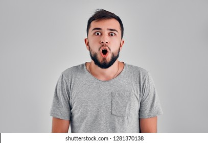 Stupefied attractive young bearded man looks with astonishment into camera, being amazed with negative news. Emotional hipster guy expresses surprisment, doesn`t believe his eyes. Facial expression