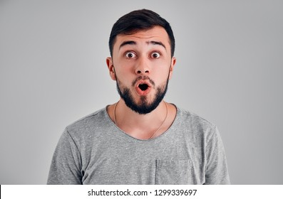 Stupefied attractive young bearded man looks with astonishment into camera, being amazed with news. Emotional hipster guy expresses surprisment, doesn`t believe his eyes. Facial expression