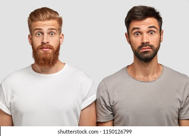 Stupefied emotive young bearded guys being astonished that friend bought expensive car. Ginger male with stupefied expression and his brother pose together against white background. Omg concept