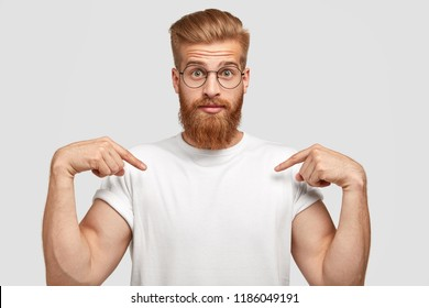 Stupefied red haired man has thick beard, points at copy space of t shirt, shows place for your slogan or logo, poses against white background. People, youth, advertisement and clothing concept