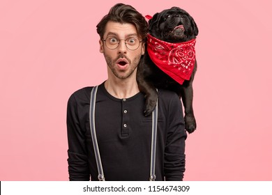 Stupefied young male carries his black pedigree dog on neck, dressed in fashionable shirt with braces, notice something surprising, isolated over pink background. Good relationships concept.
