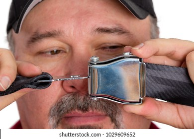 Stupid dim-witted man unable to fasten a seatbelt or perform the most simple task holding the buckle and clip in front of his face as he tries to solve the problem