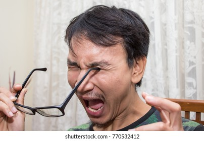 a stupid man very clumsy accidentally stab his eye with glasses leg, show painful and scream out emotional, funny accident