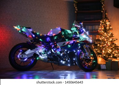 Stupino/Russia - DECEMBER 20, 2015 conceptual photo of a motorcycle as a New Year's gift. the motorbike is decorated with a multi-colored electric garland near the Christmas tree