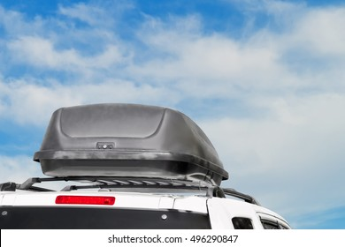 Sturdy black plastic car rooftop cargo box for traveling. Rear view of storage container mounted on white minivan roof rack. Blue sky and clouds background.