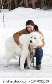 Sturdy brown-haired young man crouching on icy countryside road cuddling his huge eager Pyrenean Mountain Dog