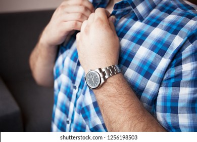 sturdy man in a blue plaid shirt with a short sleeve and a watch on his wrist buttons collar