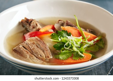 Sturdy Shurpa, Chorba or Shorba Soup with Mutton and Vegetables Close Up. Clear Homemade Halal Broth with Large Pieces of Lamb, Carrots, Potatoes, Bell Peppers, Onions, Parsley