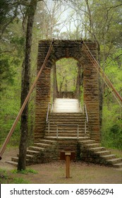 Sturdy timeworn Tishomingo stone and wood swinging bridge sits among greenery in dense forest.