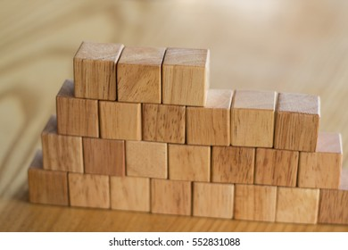 A sturdy wall constructed from wooden blocks symbolizes construction and teamwork to make something sturdy and a solid plan calls for quality materials and goals.