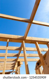 Sturdy wooden house construction of wooden building materials, construction of a frame house against the blue sky