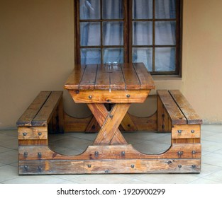 Sturdy wooden table with two seats attached as one unit standing on stoep against a window