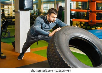 sturdy young guy pushing a big tire in the gym. man trains power fitness