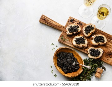 Sturgeon black caviar in wooden bowl, sandwiches and champagne on white background copy space