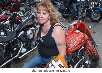 Sturgis, South Dakota - August 8, 2014: Woman Rider sitting on her bike in the city of Sturgis, in South Dakota, USA, during the annual Sturgis Motorcycle Rally