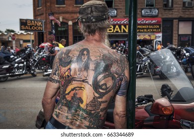 Sturgis, South Dakota - August 8, 2014: Man with a tattoed back looking at the bikes in the city of Sturgis, South Dakota, USA, during the annual Sturgis Motorcycle Rally