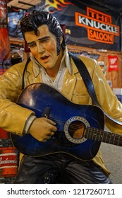 STURGIS, SOUTH DAKOTA, September 18, 2018 : An Elvis Presley statue seems to play guitar in a saloon of the town, with a lot of advertising signs in the background.