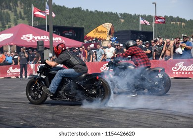 Sturgis, South Dakota / USA - August 4 2018: Two Indian motorcycle riders race against each other and create smoke during an exhibition at the Sturgis motorcycle rally.