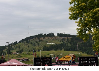 Sturgis, South Dakota / USA - August 5 2018: View of the Sturgis city sign on a hill with Indian motorcycle exhibition in the foreground during the annual Sturgis motorcycle rally.