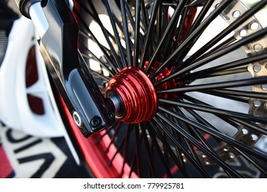 Sturgis, South Dakota / USA - August 04 2017: Closeup of a chopper motorcycle wheel with a pattern of black spokes.