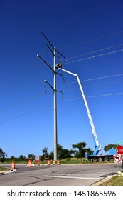 Sturtevant, Wisconsin / USA - July 15, 2019: Work installing high power transmission electrical wires continues to supply power to the Foxconn project in Racine County.  Workers remove large pullies.