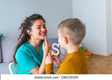 Stuttering boy and speech therapist doing exercises. Boy and young woman teacher during private home lesson. Shot of a speech therapist and a little boy