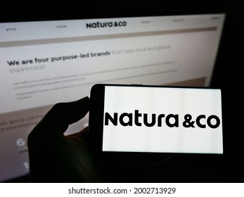 Stuttgart, Germany - 05-23-2021: Person holding mobile phone with logo of Brazilian personal care company Natura Co Holding SA on screen in front of webpage. Focus on phone display. Unmodified photo.