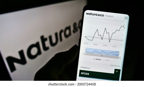 Stuttgart, Germany - 05-23-2021: Person holding cellphone with webpage of Brazilian personal care company Natura Co Holding SA on screen with logo. Focus on center of phone display. Unmodified photo.