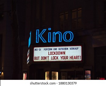 """Stuttgart, Germany - 12-19-2020: Illuminated billboard above cinema (""""Kino"""") closed due to Covid-19 lockdown in city center with slogan. Text: Popcorn and coupon sales on Mondays and Tuesdays."""