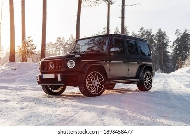 Stuttgart, Germany 19 January 2021, Mercedes-Benz G-Class (W463) Geländewagen G63 AMG Winter time in snowily forest, Driving black SUV car in snow forest road. Holiday Trip Drive to wonderland