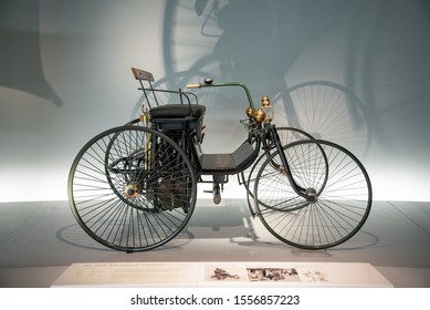 "Stuttgart, Germany - April 13, 2019: Daimler motorized quadricycle - the ""wire-wheel car"" into Mercedes-Benz Museum. Daimler and Maybach for the first time designed a completely autonomous vehicle."
