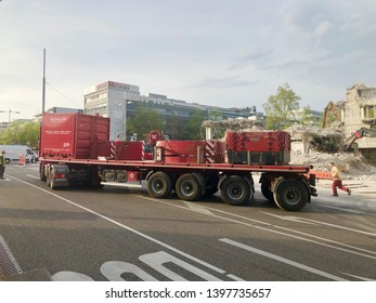 Stuttgart, Germany - April 23, 2019: A heavy transport by specialized company Scholpp carrying the weights for a crane at a site in Stuttgart with bulldozer deconstructing a building in the background
