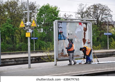 Stuttgart, Germany - April 26, 2017: Two billposters stick an advertising poster at the railway station.