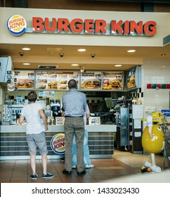 Stuttgart, Germany - Aug 15, 2018: Rear view of father and son at the counter of Burger King restaurant at Esso gas station in Germany waiting to place the order and get the fast-food away