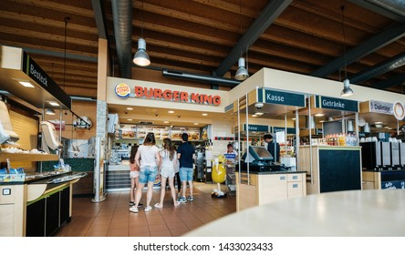 Stuttgart, Germany - Aug 15, 2018: Wide image rear view of traveller family at the counter of Burger King restaurant at Esso gas station in Germany waiting to place the order and get the fast-food
